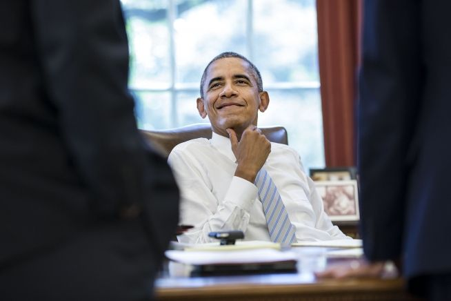 President Obama smiles in talking with advisors Sept. 18, 2015