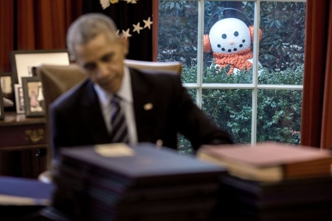 A snowman peeks into the Oval Office as President Barack Obama signs end-of-the-year bills, Dec. 16, 2016.
