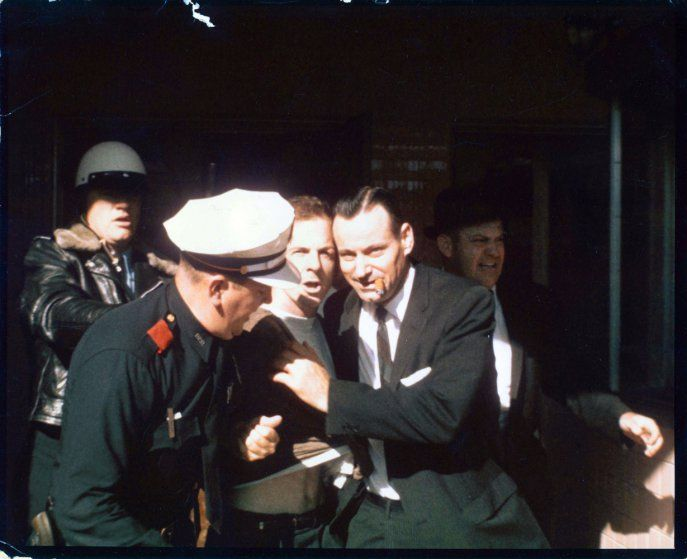 Lee Harvey Oswald, center, arrested at Texas Theatre by Dallas Det. Paul Bentley (Jim Maccammon photo)