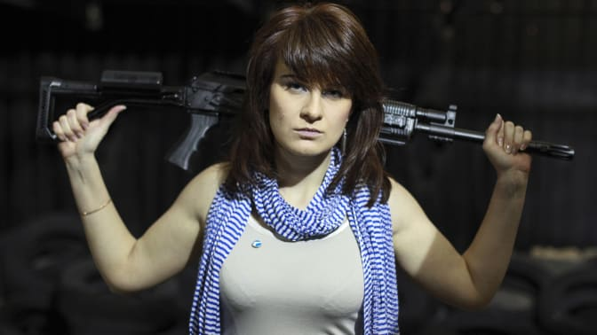 Convicted Russian agent and supposed guns rights advocate Maria Butina poses with a gun over her shoulders (Associated Press photo by Pavel Ptsitsin).